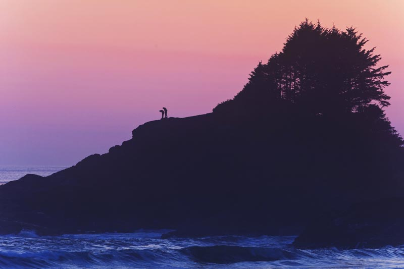 A silhouetted couple explore a rocky headland at dusk near Cox Bay